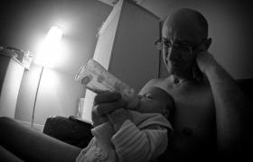 Le magicien mentaliste photographe donne le biberon a sa fille